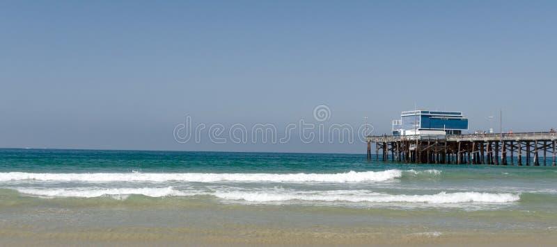 Τεμπέλικο σερφ έφαγε το Newport Beach με την προβλήτα στη γραμμή του ορίζοντα στοκ φωτογραφία με δικαίωμα ελεύθερης χρήσης