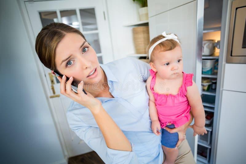 Τεντωμένη γυναίκα που μιλά στο κινητό τηλέφωνο φέρνοντας το κοριτσάκι στοκ φωτογραφίες