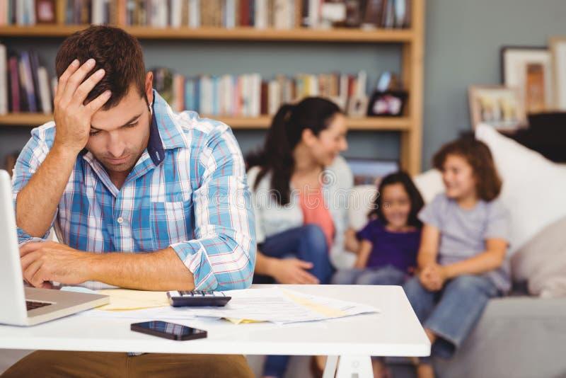 Τεντωμένο άτομο από το lap-top ενώ οικογενειακή συνεδρίαση στο υπόβαθρο στοκ εικόνες με δικαίωμα ελεύθερης χρήσης