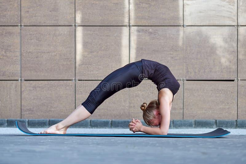 τεντώνοντας γυναίκα ικανότητα ή gymnast ή χορευτής που κάνουν τις ασκήσεις στο καφετί αστικό υπόβαθρο πόλεων τοίχων στοκ φωτογραφία