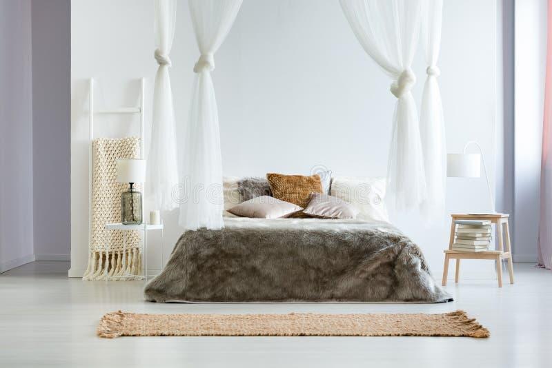 Τεράστιο κρεβάτι με το coverlet γουνών στοκ φωτογραφία