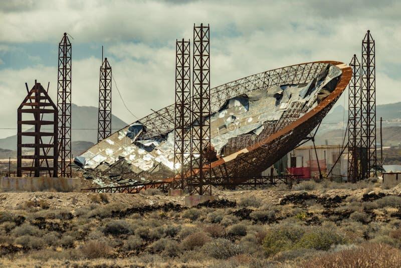 Τεράστιο παραβολικό πιάτο με τα ηλιακά πλαίσια Εγκαταλειμμένη κατασκευή για την παραγωγή enegy Χρησιμοποιημένος για την παραγωγή  στοκ φωτογραφία με δικαίωμα ελεύθερης χρήσης