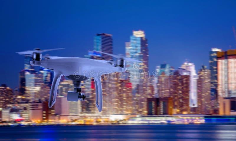 Τετράγωνο κηφήνων copter με τη κάμερα που πετά προς το κέντρο πόλεων στη νύχτα στοκ εικόνες