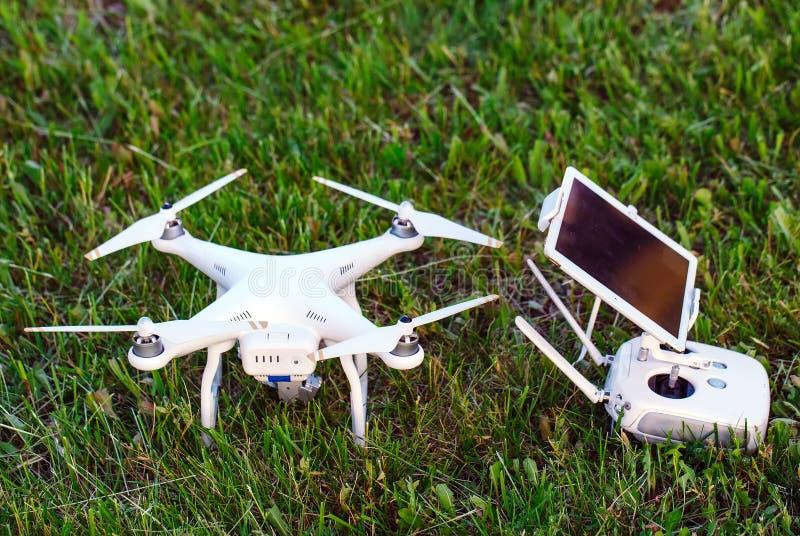 Τετράγωνο κηφήνων copter με τη ψηφιακή κάμερα υψηλής ανάλυσης και το μαξιλάρι τηλεχειρισμού του με το smartphone στη χλόη στοκ φωτογραφίες