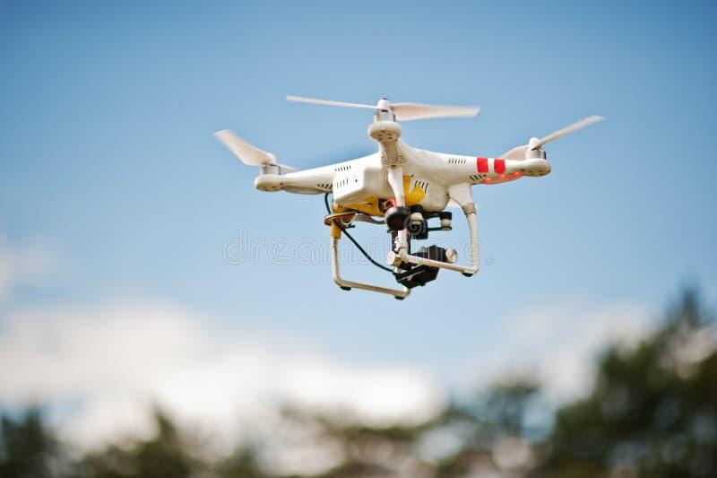 Τετράγωνο κηφήνων copter με τη ψηφιακή κάμερα υψηλής ανάλυσης που πετά μέσα στοκ εικόνα
