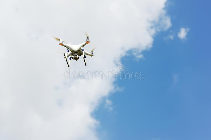 Τετράγωνο κηφήνων copter με το πέταγμα ψηφιακών κάμερα που αιωρείται στο μπλε ουρανό στοκ εικόνα