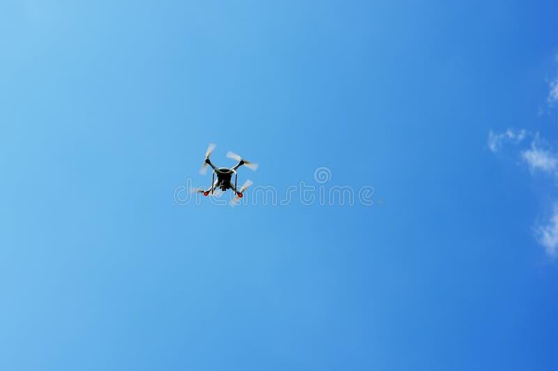 Τετράγωνο κηφήνων copter με το πέταγμα ψηφιακών κάμερα που αιωρείται στο μπλε ουρανό στοκ φωτογραφία