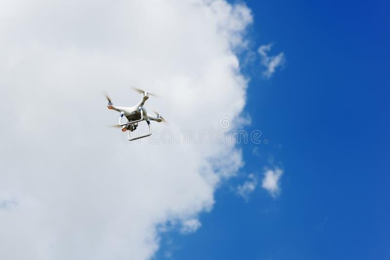 Τετράγωνο κηφήνων copter με το πέταγμα ψηφιακών κάμερα που αιωρείται στο μπλε ουρανό στοκ εικόνες με δικαίωμα ελεύθερης χρήσης