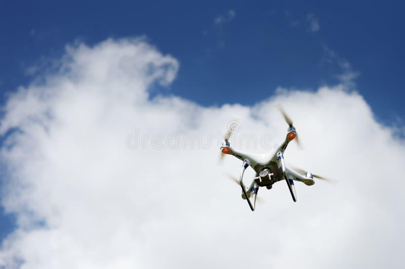 Τετράγωνο κηφήνων copter με το πέταγμα ψηφιακών κάμερα που αιωρείται στο μπλε ουρανό στοκ φωτογραφία με δικαίωμα ελεύθερης χρήσης