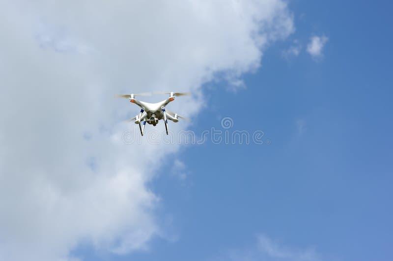 Τετράγωνο κηφήνων copter με το πέταγμα ψηφιακών κάμερα που αιωρείται στο μπλε ουρανό στοκ φωτογραφίες