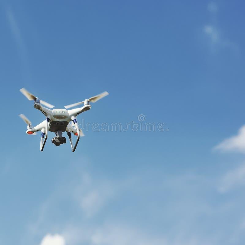 Τετράγωνο κηφήνων copter με το πέταγμα ψηφιακών κάμερα που αιωρείται στο μπλε ουρανό στοκ εικόνα με δικαίωμα ελεύθερης χρήσης