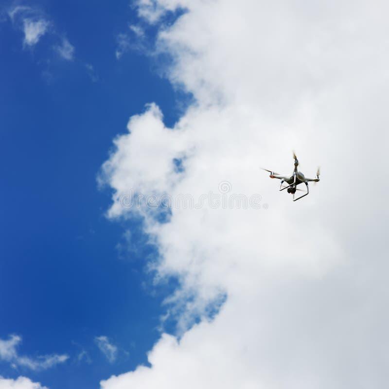 Τετράγωνο κηφήνων copter με το πέταγμα ψηφιακών κάμερα που αιωρείται στο μπλε ουρανό στοκ εικόνες