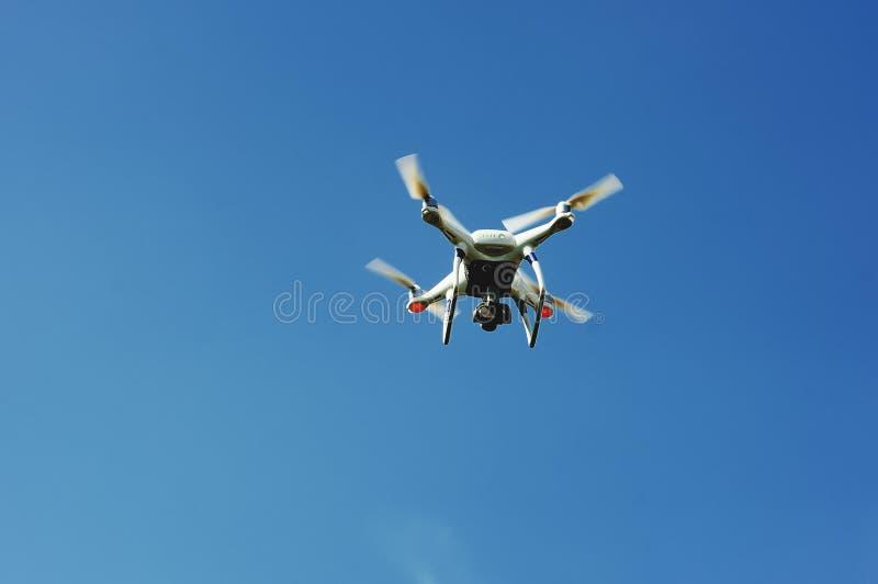 Τετράγωνο κηφήνων copter με το πέταγμα ψηφιακών κάμερα που αιωρείται στο μπλε ουρανό στοκ φωτογραφίες με δικαίωμα ελεύθερης χρήσης
