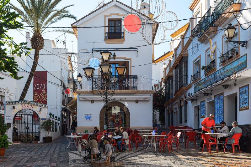 Τετράγωνο Χριστουγέννων με το μικρό καφέ μεταξύ των στενών οδών της ηλιόλουστης πόλης Marbella, Ανδαλουσία, Ισπανία στοκ φωτογραφίες με δικαίωμα ελεύθερης χρήσης