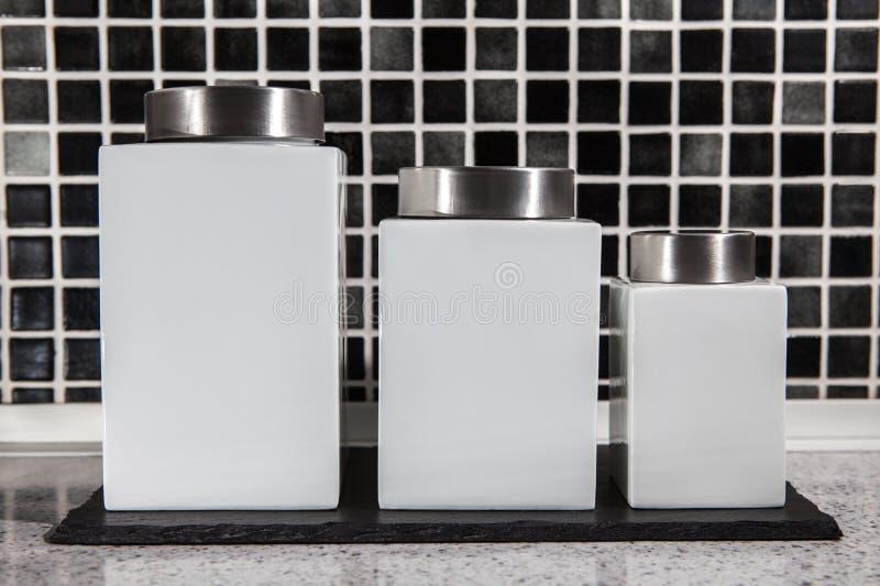 Τετραγωνικά άσπρα βάζα αποθήκευσης σε γραπτό που κεραμώνονται σύγχρονο kitche στοκ εικόνες