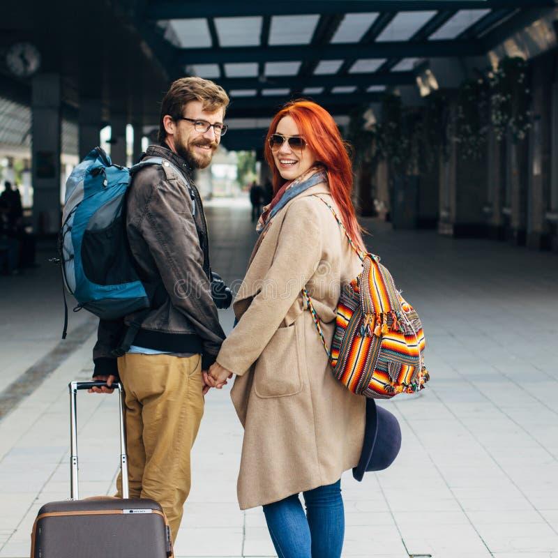 Τετραγωνική φωτογραφία Πραγματική άποψη του ερωτικού ζεύγους hipster που περπατά κάτω από το σταθμό και που κουβεντιάζει υπαίθρια στοκ εικόνες