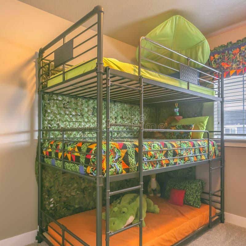 Τετραγωνικό άνετο εσωτερικό δωματίων με ένα ζωηρόχρωμο τριπλό κρεβάτι κουκετών για τα παιδιά στοκ φωτογραφίες με δικαίωμα ελεύθερης χρήσης