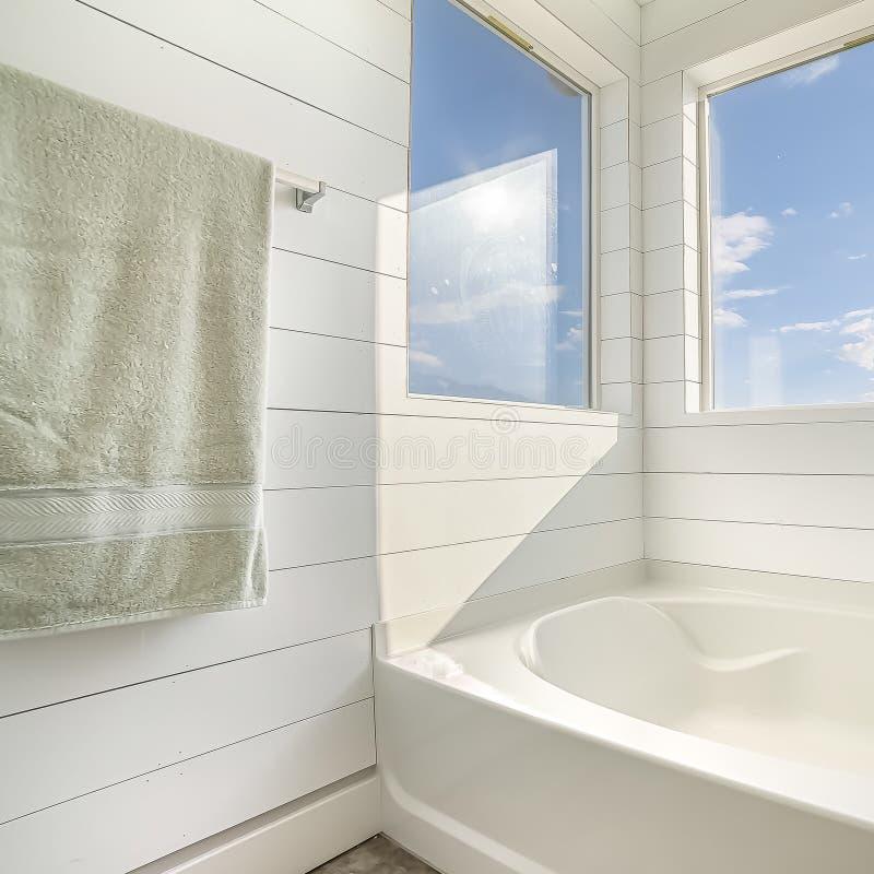 Τετραγωνικό εσωτερικό σχέδιο λουτρών πλαισίων μινιμαλιστικό με την άσπρη μπανιέρα και τον άσπρο τοίχο στοκ εικόνα