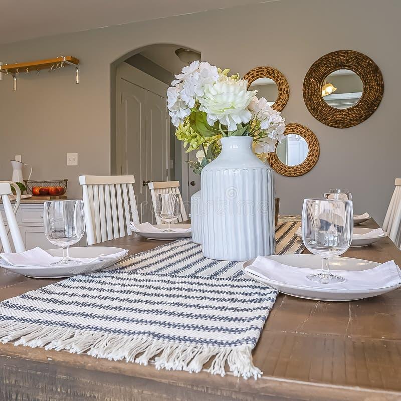 Τετραγωνικό εσωτερικό τραπεζαρίας με τον καφετή ξύλινο πίνακα και τις άσπρες ξύλινες καρέκλες στοκ εικόνες