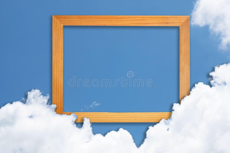 Τετραγωνικό ξύλινο πλαίσιο, δημιουργικός όμορφος μπλε ουρανός με τα άσπρα σύννεφα για το υπόβαθρο με τη σημείωση καρτών εγγράφου στοκ φωτογραφία με δικαίωμα ελεύθερης χρήσης