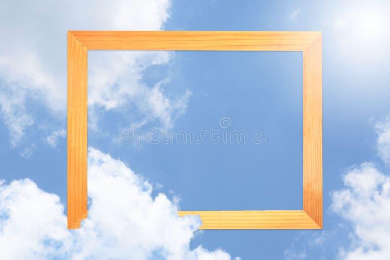 Τετραγωνικό ξύλινο πλαίσιο, δημιουργικός όμορφος μπλε ουρανός με τα άσπρα σύννεφα για το υπόβαθρο με τη σημείωση καρτών εγγράφου ελεύθερη απεικόνιση δικαιώματος