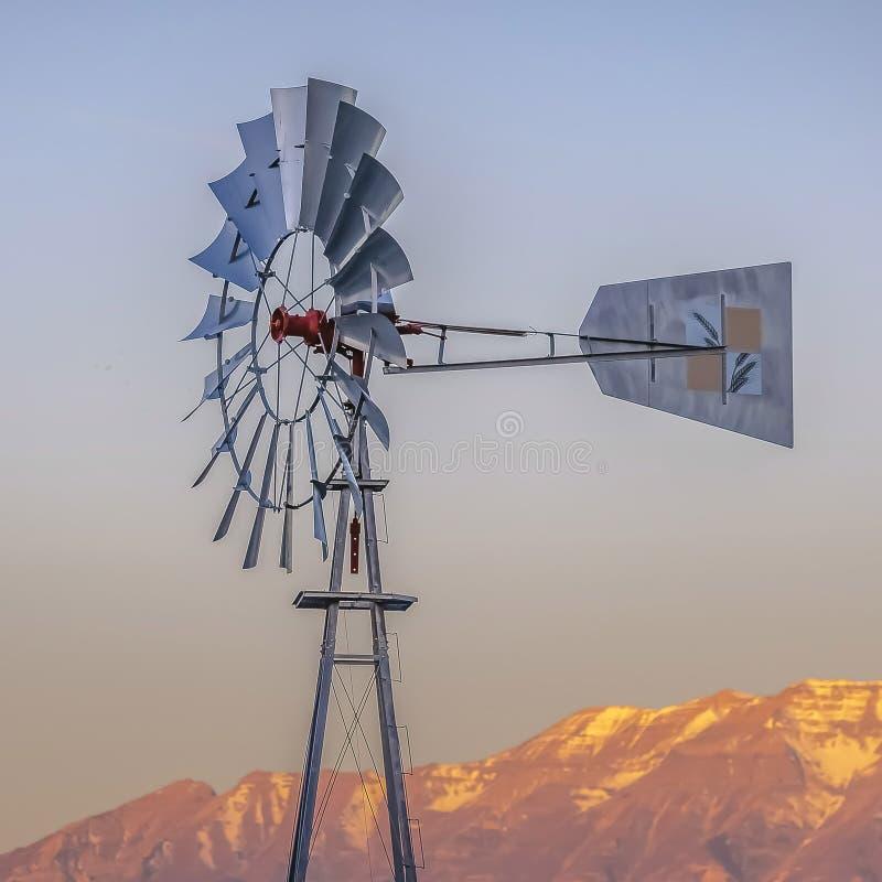 Τετραγωνικό Windpump με ένα τραχύ χρυσό βουνό και ένα νεφελώδες υπόβαθρο ουρανού στοκ εικόνα με δικαίωμα ελεύθερης χρήσης