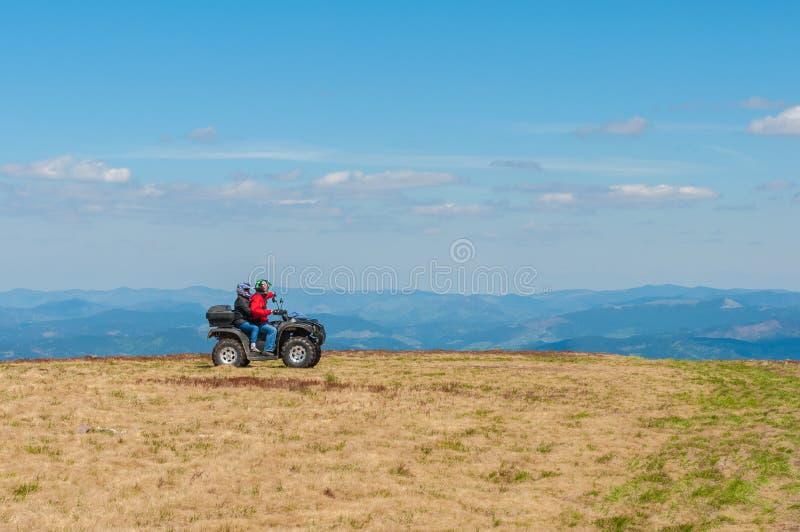 Τετραγώνων στα βουνά Εξοπλισμένος οδηγός ATV στοκ φωτογραφία
