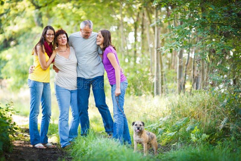 Τετραμελής οικογένεια με ένα χαριτωμένο σκυλί υπαίθρια στοκ εικόνα