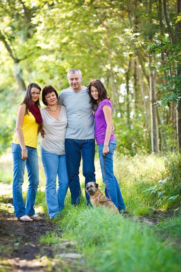 Τετραμελής οικογένεια με ένα χαριτωμένο σκυλί υπαίθρια στοκ εικόνες