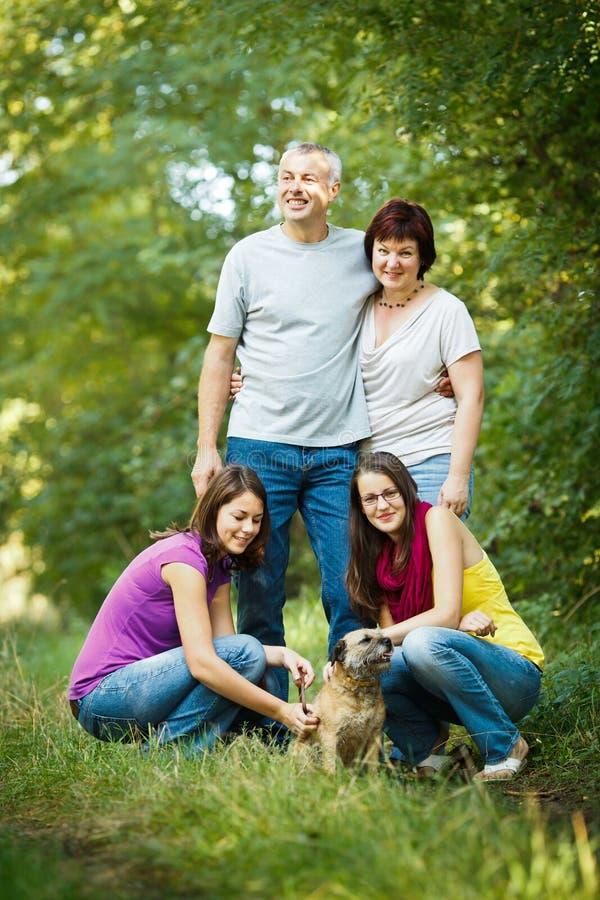Τετραμελής οικογένεια με ένα χαριτωμένο σκυλί υπαίθρια στοκ φωτογραφίες με δικαίωμα ελεύθερης χρήσης