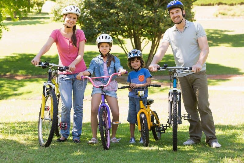 Τετραμελής οικογένεια με τα ποδήλατα στο πάρκο στοκ εικόνες