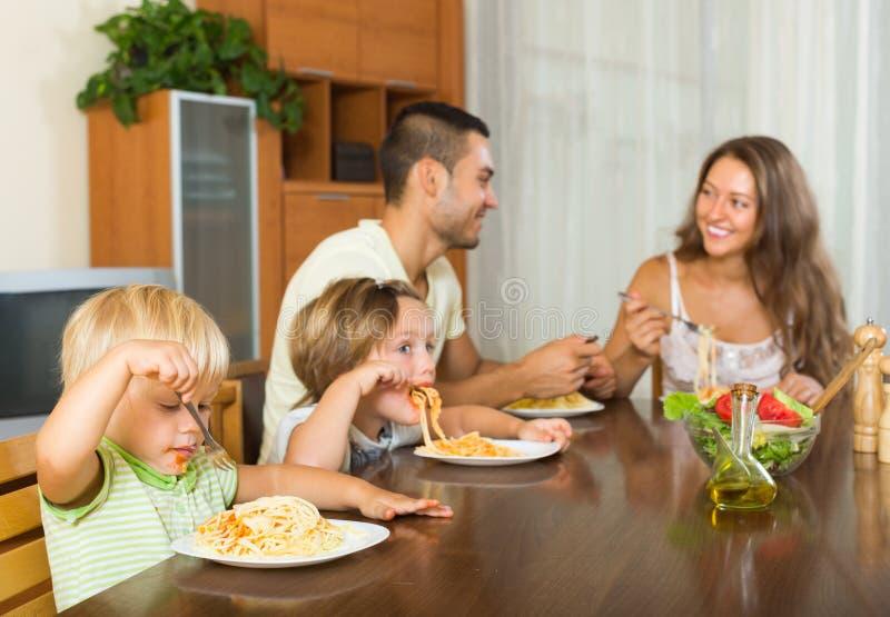 Τετραμελής οικογένεια που τρώει τα μακαρόνια στοκ εικόνα