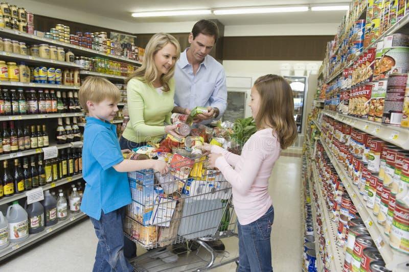 Τετραμελής οικογένεια που ψωνίζει στην υπεραγορά στοκ εικόνες