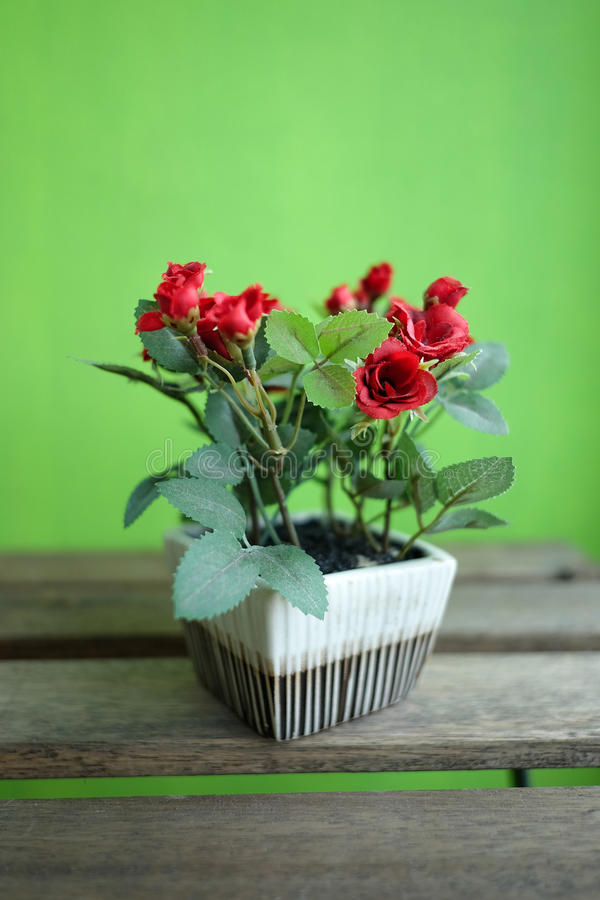 Τεχνητά κόκκινα τριαντάφυλλα στον ξύλινο πίνακα με το πράσινο υπόβαθρο στοκ φωτογραφία με δικαίωμα ελεύθερης χρήσης