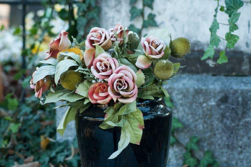 τεχνητά λουλούδια στον τάφο στο νεκροταφείο στοκ φωτογραφίες