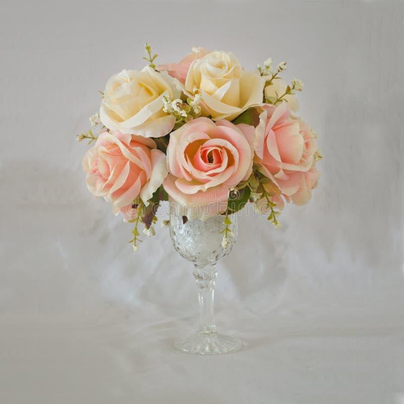 Τεχνητά λουλούδια βάζων τριαντάφυλλων στο βρώμικο υπόβαθρο στοκ εικόνα