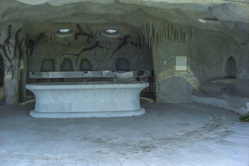 Τεχνητή σπηλιά στον κήπο ως υπαίθριο roo κουζινών και συνεδρίασης στοκ φωτογραφία