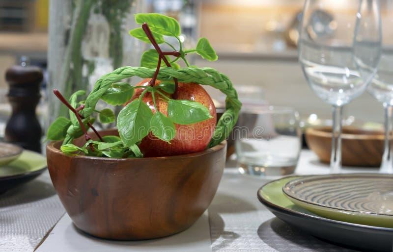 Τεχνητό κόκκινο μήλο σε ένα ξύλινο πιάτο στον πίνακα στοκ φωτογραφίες
