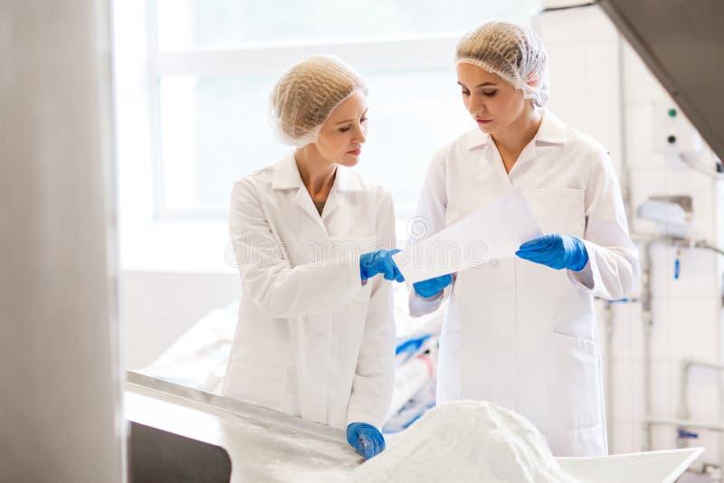 Τεχνικοί γυναικών που εργάζονται στο εργοστάσιο παγωτού στοκ εικόνα