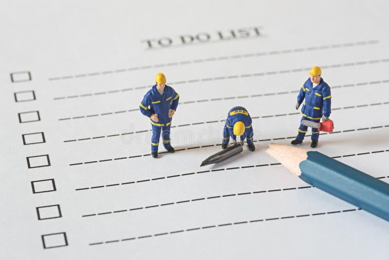 Τεχνικοί μικροσκοπικοί άνθρωποι αριθμών για να γίνει ο κατάλογος με ένα σπασμένο π στοκ εικόνες με δικαίωμα ελεύθερης χρήσης