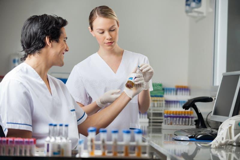 Τεχνικοί που αναλύουν το δείγμα στο ιατρικό εργαστήριο στοκ εικόνα