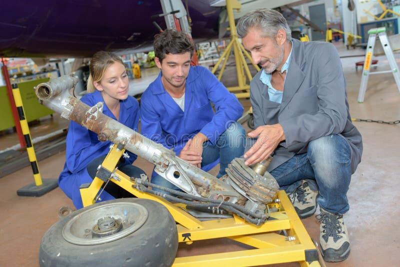 Τεχνικοί που εξετάζουν το αποσυναρμολογημένο προσγειωμένος εργαλείο αεροσκαφών στοκ εικόνες με δικαίωμα ελεύθερης χρήσης