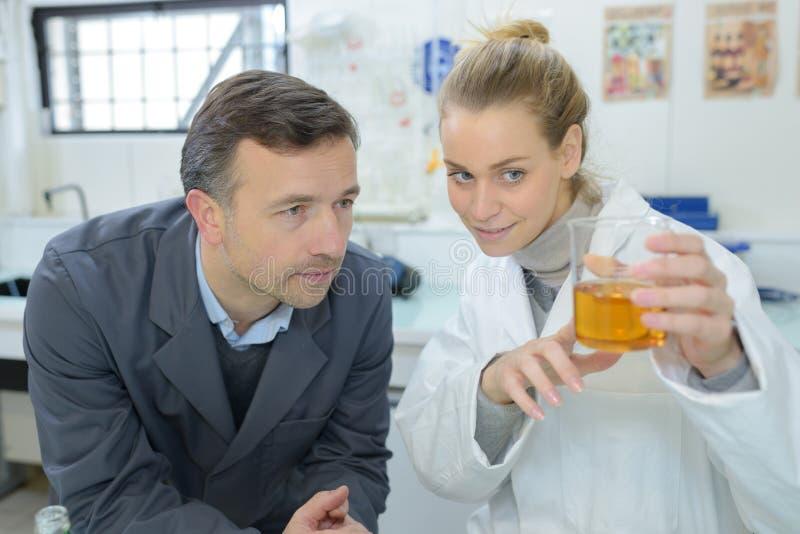 Τεχνικοί που εξετάζουν το κίτρινο υγρό στην κούπα γυαλιού στοκ εικόνες με δικαίωμα ελεύθερης χρήσης