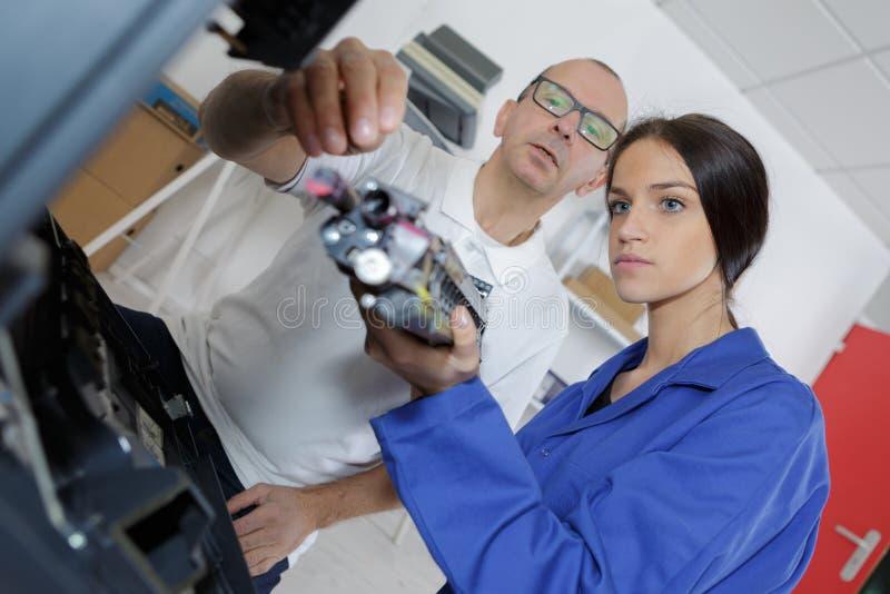Τεχνικοί που επισκευάζουν την ψηφιακή μηχανή φωτοτυπικών μηχανημάτων στοκ φωτογραφία με δικαίωμα ελεύθερης χρήσης