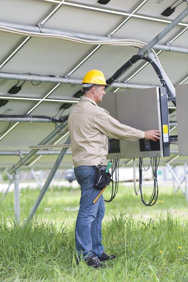 Τεχνικοί που εργάζονται κάτω από τα ηλιακά πλαίσια στοκ φωτογραφίες