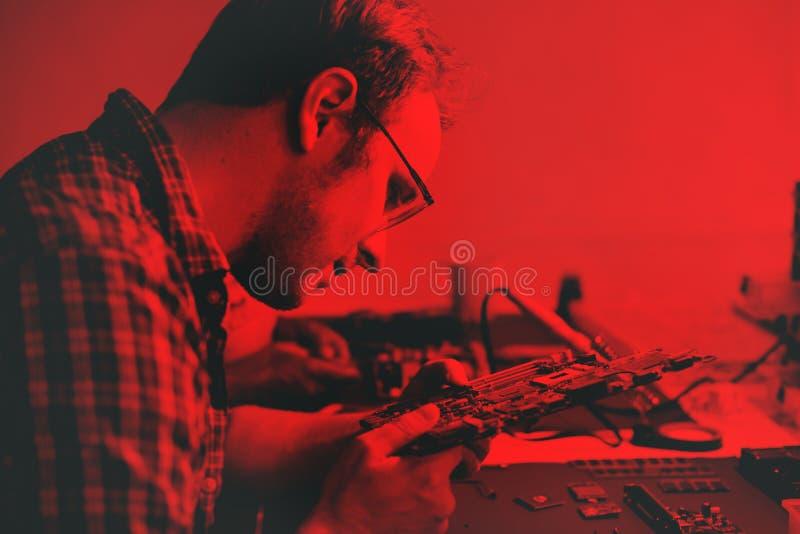 Τεχνικοί που εργάζονται στα μέρη ηλεκτρονικής στοκ εικόνα με δικαίωμα ελεύθερης χρήσης