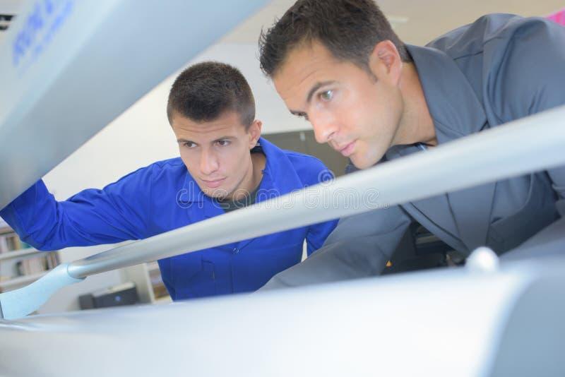 Τεχνικοί που εργάζονται στη μηχανή στοκ φωτογραφία