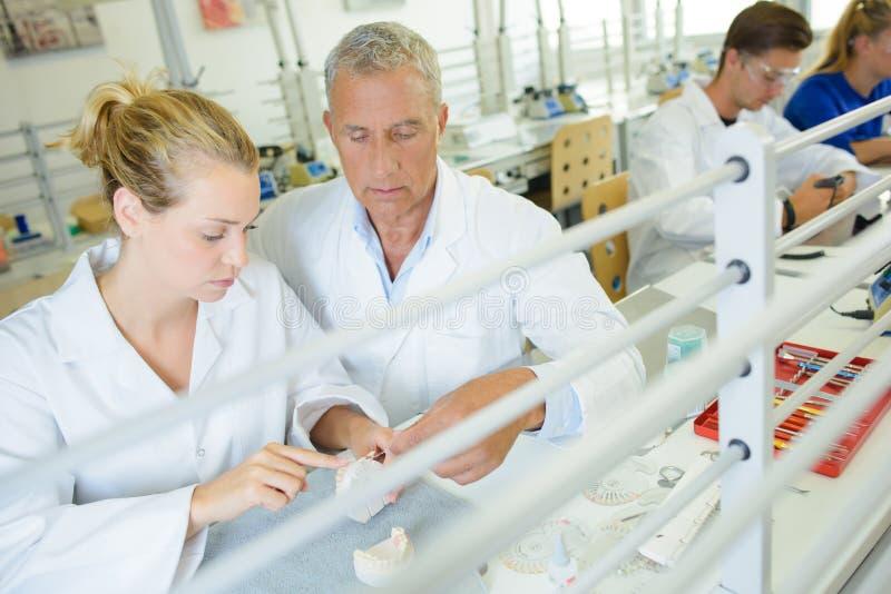 Τεχνικοί που εργάζονται στο οδοντικό εργαστήριο στοκ εικόνα με δικαίωμα ελεύθερης χρήσης
