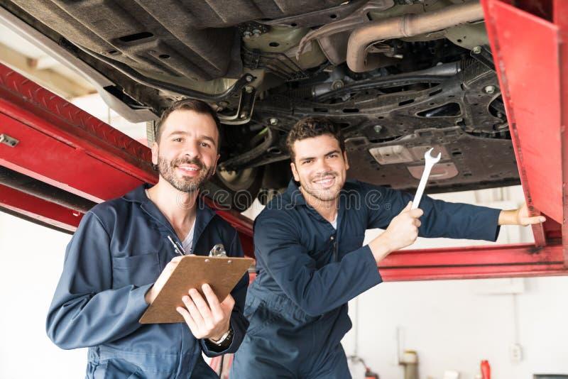 Τεχνικοί που χαμογελούν ενώ κάτω από το αυτοκίνητο στο γκαράζ στοκ φωτογραφία με δικαίωμα ελεύθερης χρήσης