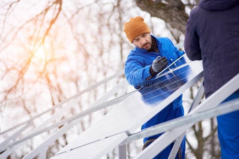 Τεχνικοί στα μπλε κοστούμια που εγκαθιστούν τις φωτοβολταϊκές ηλιακές ενότητες στη στέγη του σύγχρονου σπιτιού στοκ φωτογραφία
